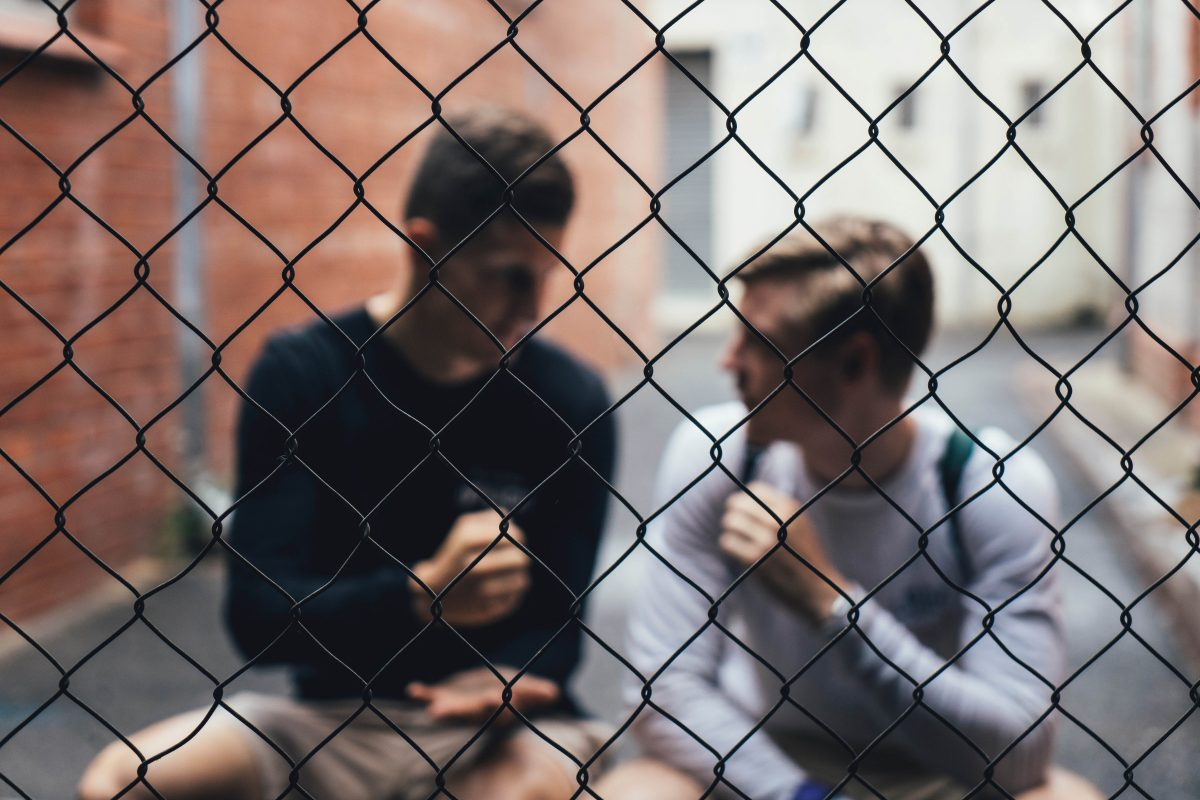 two guys sitting behind wire fence