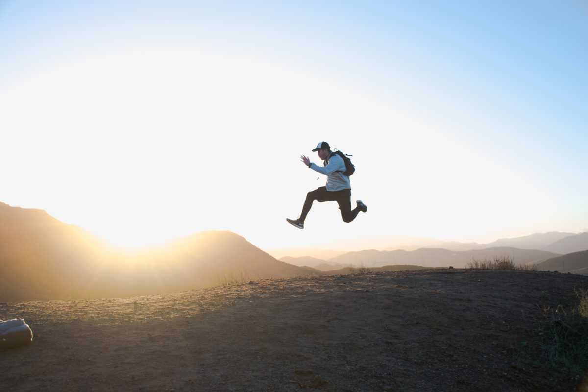 person jumping on top of a hill